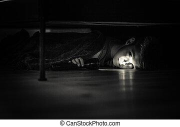 triste, menino jovem, com, lanterna, mentindo, sob, seu, cama