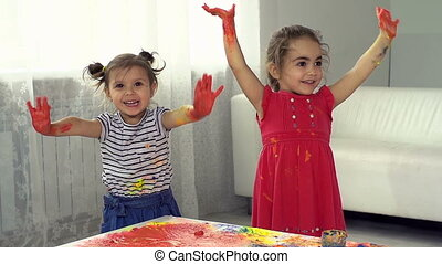 Triumph of Color - Two joyful kids showing their blotted...