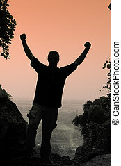 Triumph - Silhouette of man at viewpoint with arms raised