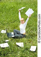 Triumph - Portrait of joyful female sitting on green grass...