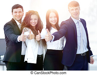 triumphant business team holding thumbs up - concept of...