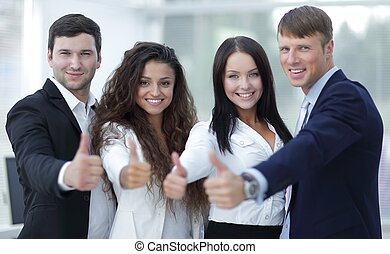 triumphant business team holding thumbs up