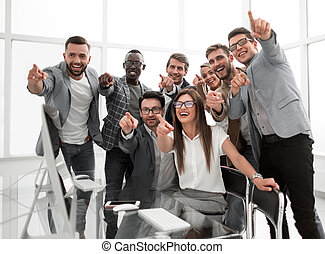 triumphant business team pointing at you.concept of success