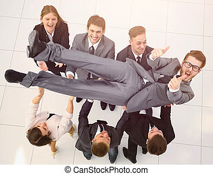 triumphant business team shakes their leader - concept of...
