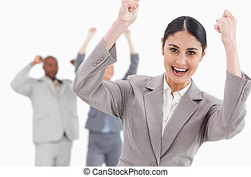 Triumphant businesswoman with cheering associates behind her