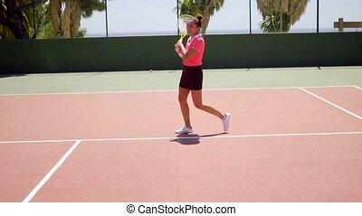 Triumphant young female tennis player cheering and walking...