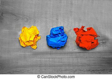 trois, balles, de, chiffonné, papier coloré, sur, a, table bois