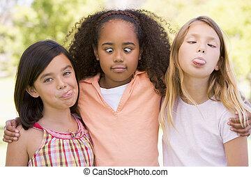 trois, jeune fille, amis, dehors, fabrication visages drôles
