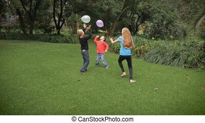 trois, mignon, gosses, jouer ensemble, dans, a, parc, à, ballons, dans, slowmo