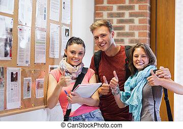 trois, sourire, étudiants, debout, côté, panneau affichage, projection, pouces haut, dans, école