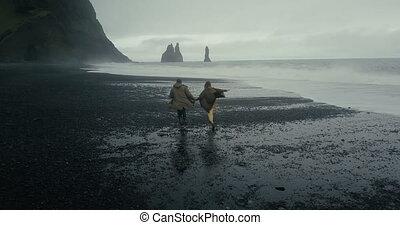 troll, volcanique, aérien, couple, iceland., jeune, dos, courant, orteils, hipster, noir, plage, vue