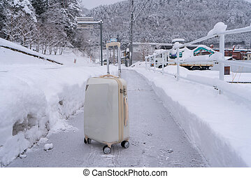 Trolley luggage on the road with snow ground at Gifu Japan