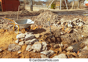 Trolley, shovel, pit,  sand, stones and ground near the building is under construction with new foundation