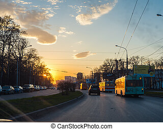 Trolleybus on street road with sunset sky in city