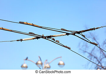 Trolleybus wires against the blue sky in the city