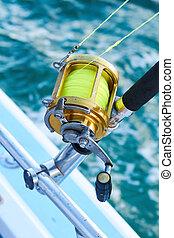 Trolling fishing boat rod and golden saltwater reel deep blue ocean sea wake. Dominican Republik Punta Cana Fishing boat.