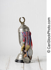 Trophy full of medals over white wall