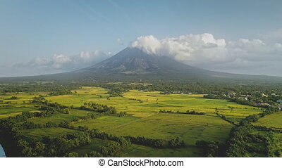 Tropic river with green banks at Mayon volcano eruption aerial. Greenery meadow at fog haze of Philippines mountain at Legazpi town. Rurar fields at stream. Filipino tourist landmark at countryside