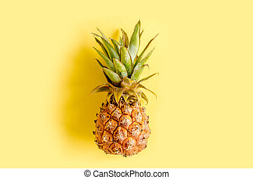 Tropical abstract background, pattern with coconut and pineapple, on yellow background. Summer concept. Flat lay, top view.