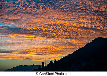 tropical autumn sunset with mountain range silhouette