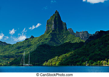 View from the water of the tropical bay on Moorea with a sailboat anchored. Moorea Island Roto Nui Volcanic Mountain pushes towards the sky.