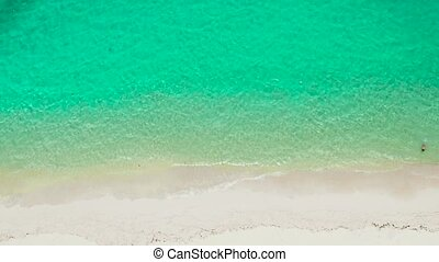 Tropical sandy beach with wave and turquoise water,copy space for text, aerial view. Sea water surface in lagoon. Transparent turquoise ocean water surface. Background texture