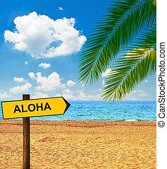 Tropical beach and direction board saying ALOHA