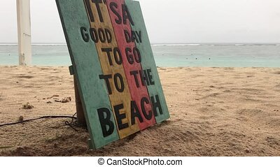 Tropical beach in a rainy day. Wooden plate with text it is a good day to go to the beach. Bali island.