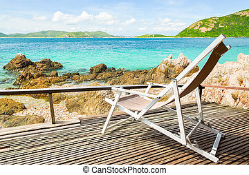 Tropical beach landscape with chairs for relaxation on wooden terrace.