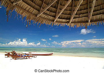 Tropical beach resort with bamboo hut in the foreground