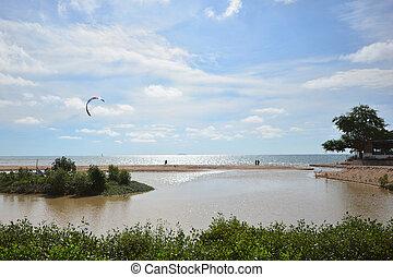 Tropical Beach Sea, Sand, Sun with paramotor flying over the beach with blue sky.
