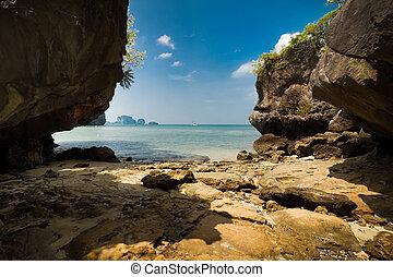 Tropical beach view from karst limestone cave. Ocean...