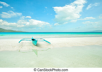 Tropical beach with a boat on the white sand