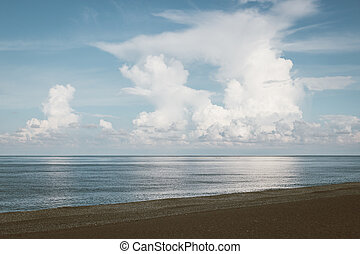 tropical beach with blue sky and cumulus clouds