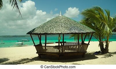 Tropical beach with bungalow under palm trees of Daco, Philippines. Summer and travel vacation concept