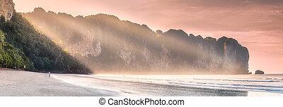 Tropical beach with sunbeams on sand coast of sea