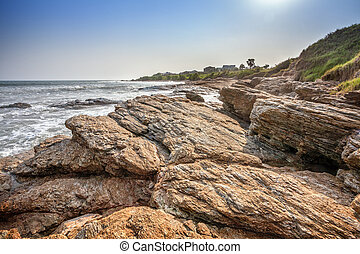 Tropical beach with waves crashing on rocks in West Africa