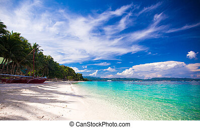 Tropical beach with white sand and a small boat