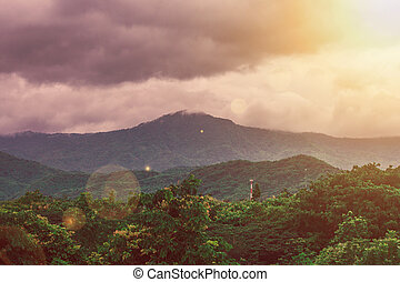 Tropical beautiful landscape view of misty rainforest mountain in cloudy day with sunlight radiate from top left corner.
