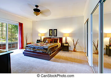 Beautiful tropical theme bedroom with a carpet floor, mirror door closet and walkout deck