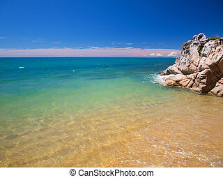 Tropical Blue Sea - Rocky Outcrop on a Tropical Beach with...