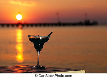 Tropical cocktail overlooking a sunset ocean