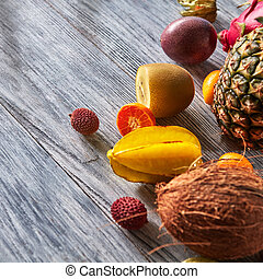 Group of exotic tropical fruits. Kiwi, dragon fruit, passion fruit, coconut, pineapple, carambola, kumquat on a gray background, copy space. Concept of healthy dieting food.