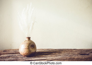 Tropical dried flowers in vase over grunge background