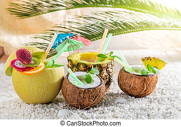 Tropical drinks in fresh fruits with cocktail umbrellas