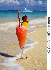 tropical drink in hawaii on the sand at water's edge
