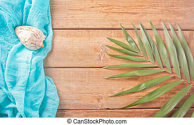 Tropical exotic palm leaves, blue cloth and seashell on wooden background. Copy space. Top view.