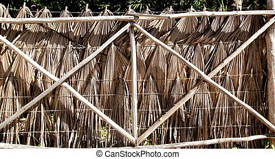 tropical fence palm tree leaves and wood trunks - tropical...