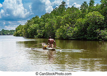 Tropical forest on the river bank .Fisherman floating in a boat.