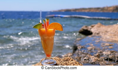 Tropical Fresh Juice in a Glass with Straw on the Beach of...